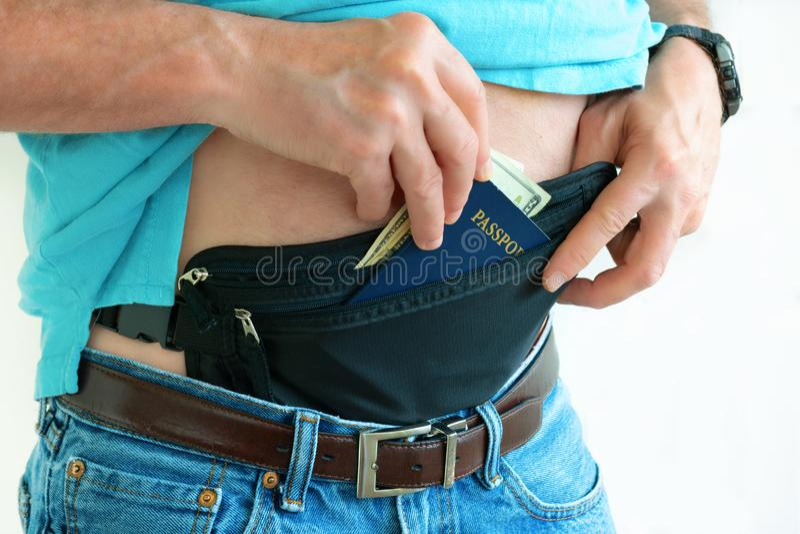 Man getting cash and passport from hidden travel money belt stock image