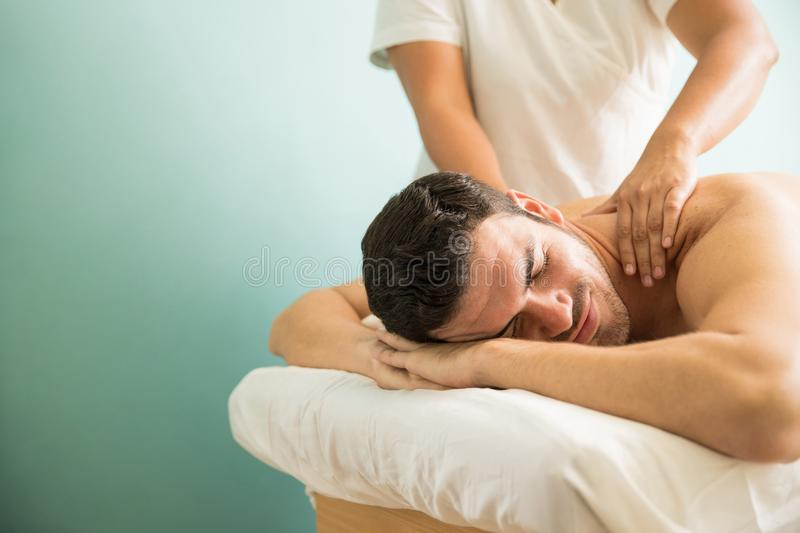 Man getting a deep tissue massage. Young men looking happy and relaxed while getting a relaxing massage at a spa. Lots of copy space stock photography