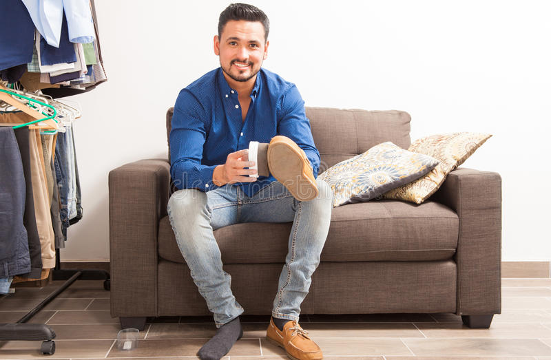 Man getting dressed and polishing his shoes. Portrait of a young Hispanic man with a beard polishing his shoes in a dressing room and getting ready for work stock photo