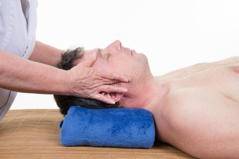 Man getting a facial face massage at day spa by woman stock photo