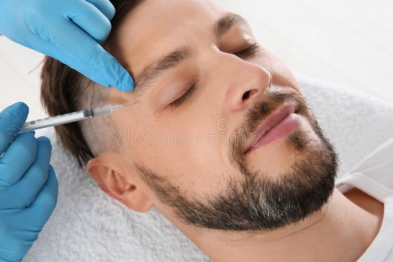 Man getting facial injection in clinic. Cosmetic surgery concept stock images