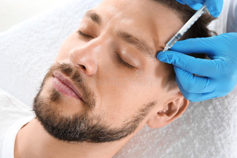 Man getting facial injection in clinic. Cosmetic surgery concept royalty free stock photo