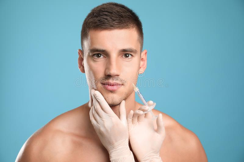 Man getting facial injection on  blue background. Cosmetic surgery. Man getting facial injection on light blue background. Cosmetic surgery royalty free stock photography