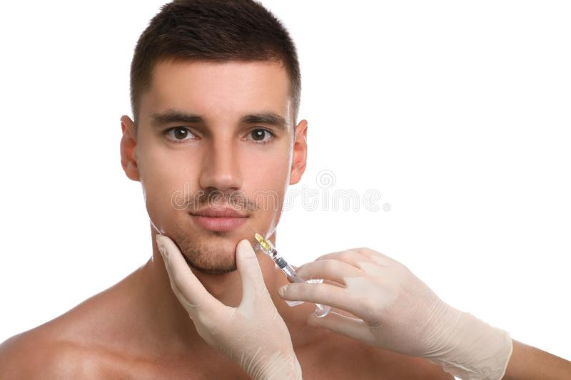 Man getting facial injection on white background. Cosmetic surgery royalty free stock photography