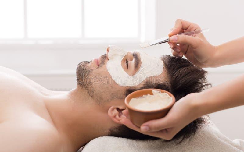 Man getting facial nourishing mask at spa salon. Unshaven man getting facial nourishing mask by beautician at spa salon stock photo