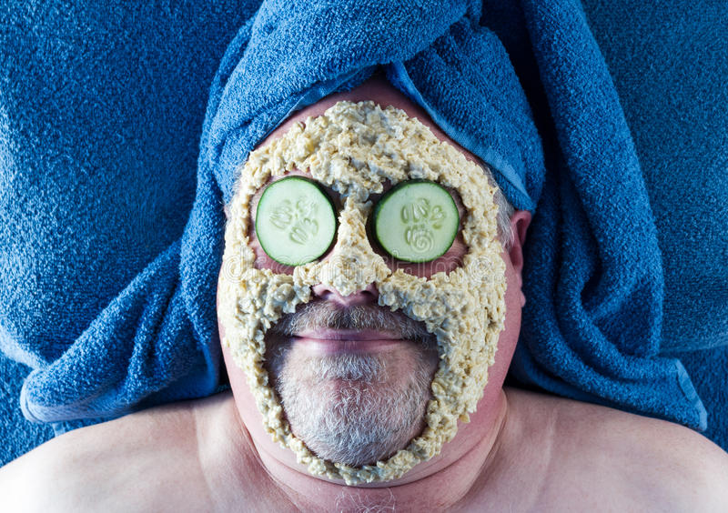 Man Getting Facial. Man getting oatmeal mask facial with cucumber slices on his eyes royalty free stock photo