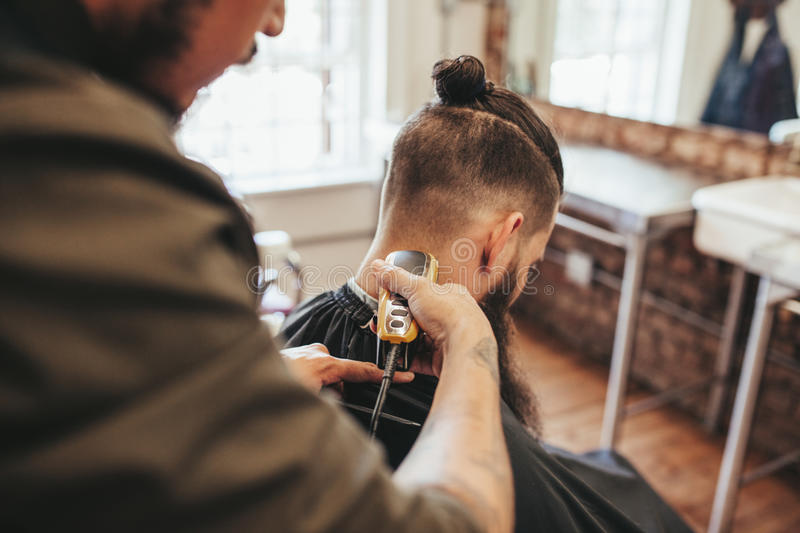 Man getting haircut by barber at salon. Hairdresser cutting hair of client with hair trimmer machine royalty free stock photo