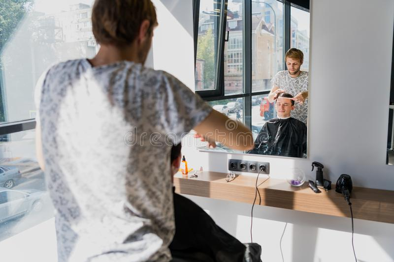 Man getting haircut at barber shop. Hairdresser styling hair of customer at salon. stock photo