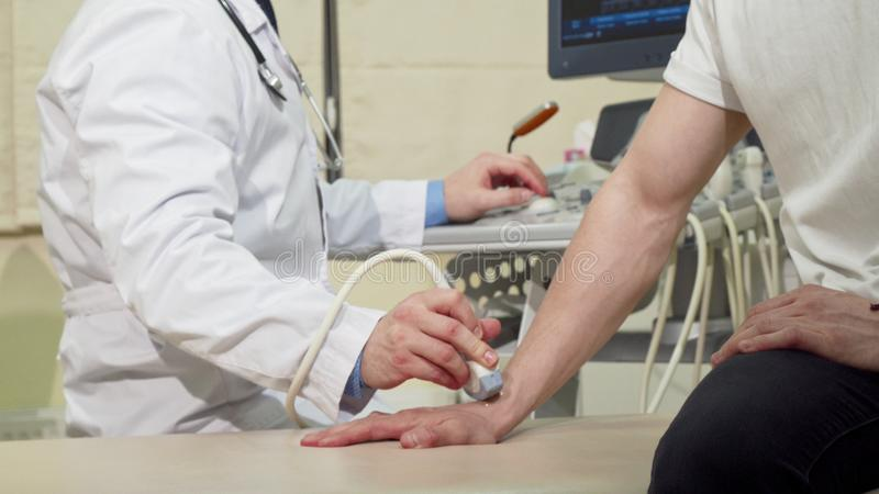 Man getting his wrist bones checked by doctor using ultrasound scanner. Cropped shot of a men on medical appointment, doctor examining his wrist with royalty free stock photography