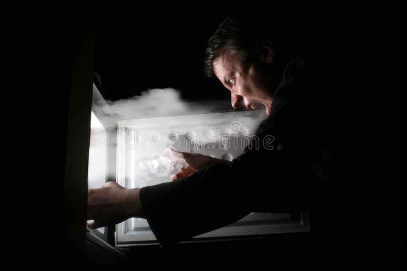 Man getting ice. A man getting ice from the fridge stock image