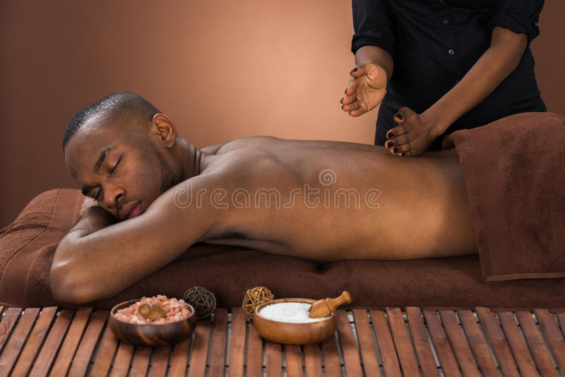 Man Getting Massage In Spa. Young African Man Getting Massage In Spa royalty free stock photos