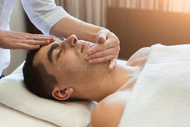 Man getting professional facial massage at spa salon royalty free stock images