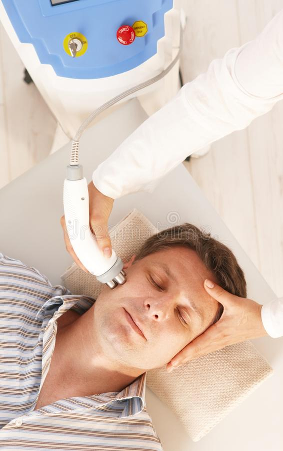 Man getting radio frequency treatment. Man getting radio frequency fat reduction treatment in day spa stock photos