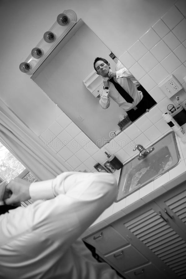 Man Getting Ready. A man in a shirt and tie in the bathroom getting ready to go. Shallow depth of field royalty free stock photo