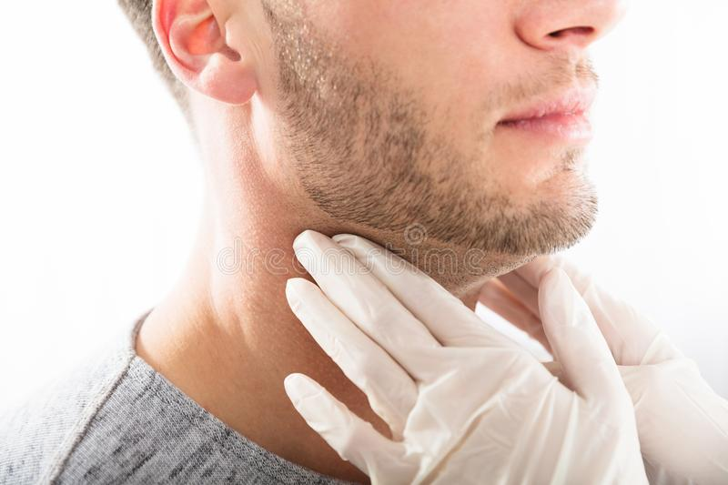 Man Getting Thyroid Gland Control. Doctor Performing Physical Exam Palpation Of The Thyroid Gland royalty free stock photo