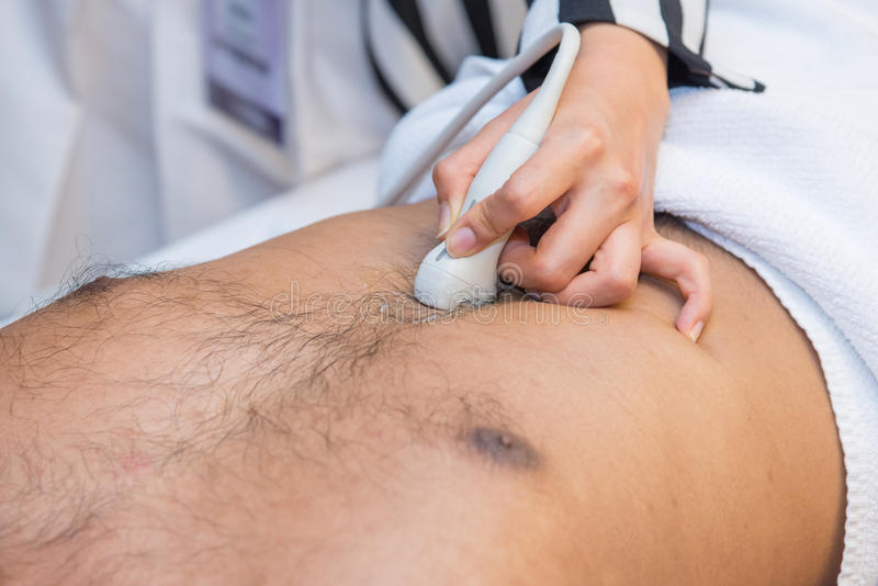 Man getting an ultrasound scan. Closeup of man getting an ultrasound scan on abdominal by doctor stock images