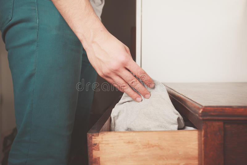 Man getting underwear from drawer. A young man is getting underwear out of his drawer stock photography