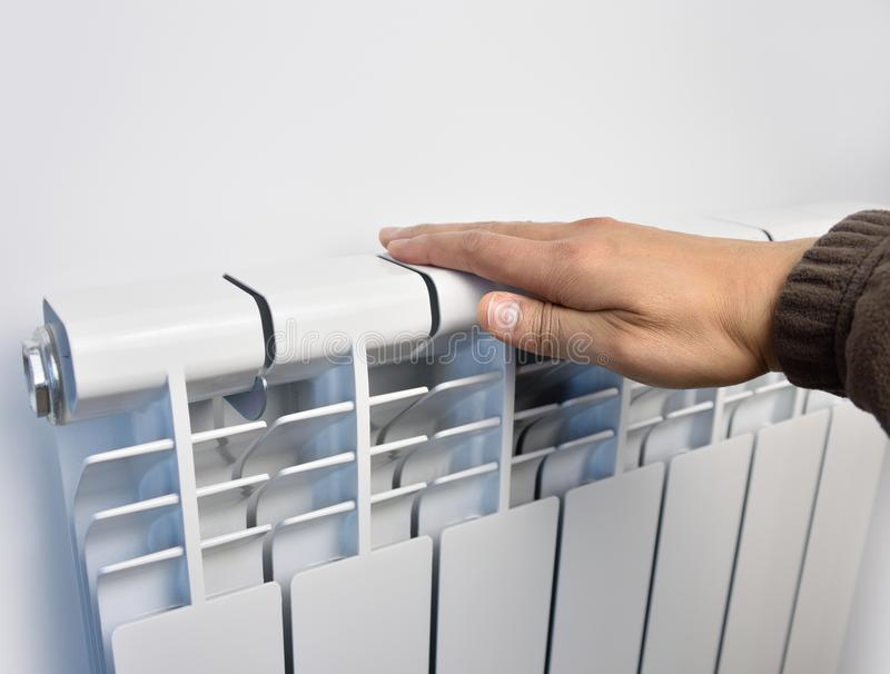 Ecological heating at home. Man getting warm up his hand over an electric radiator of heating at home royalty free stock images