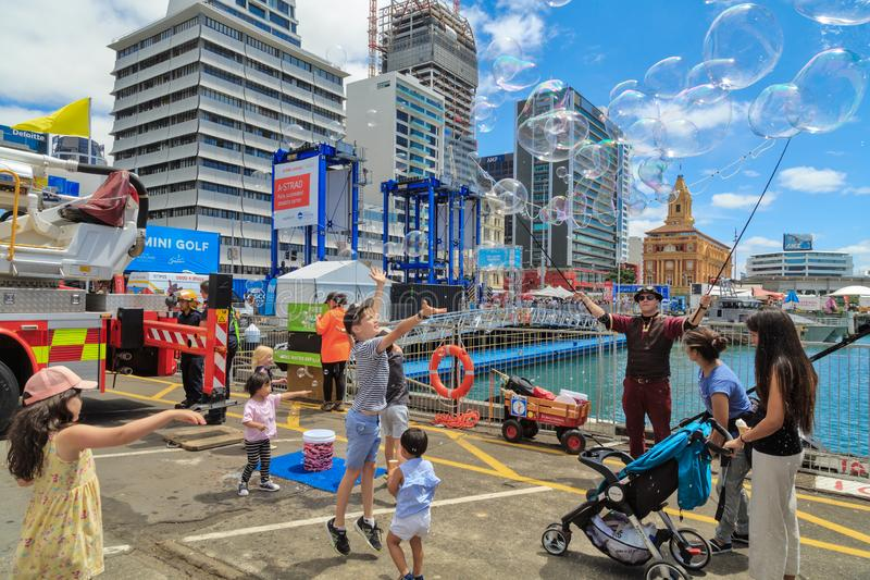 Man with giant bubble maker entertaining children. An entertainer making giant soap bubbles on the waterfront in Auckland, New Zealand, during Auckland stock photo