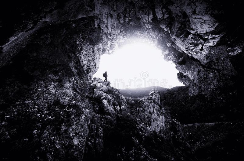 Man at giant cave entrance with steep cliffs. Man exploring cave. Giant cave entrance with man. Steep cliffs at giant cave entrance royalty free stock image