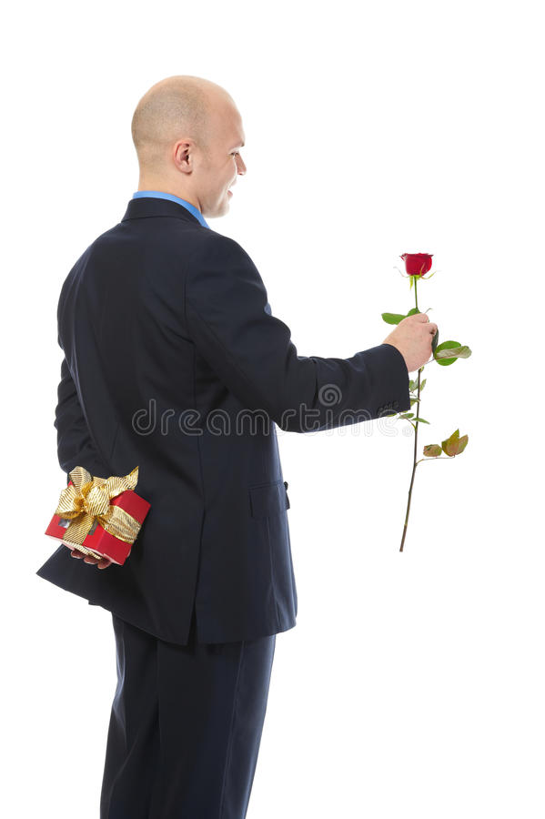 Man with a gift box and a rose. Isolated on white background stock photography