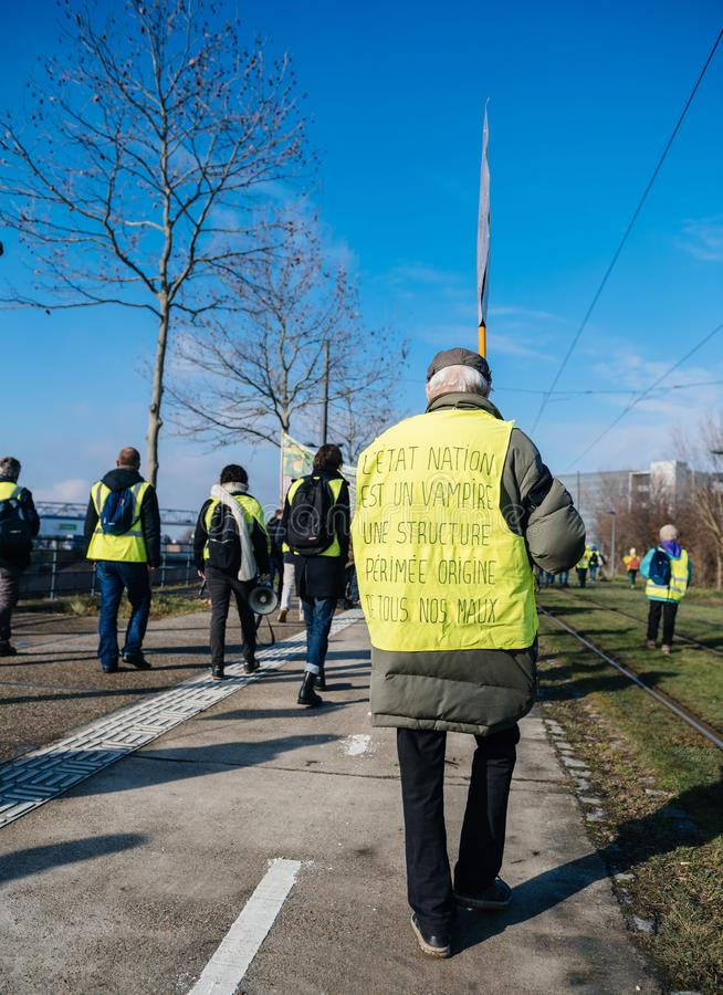Man in Gilets Jaunes Yellow Vest with inscription the state is a vampire. STRASBOURG, FRANCE - FEB 02, 2018: Man in Gilets Jaunes Yellow Vest with inscription royalty free stock photo