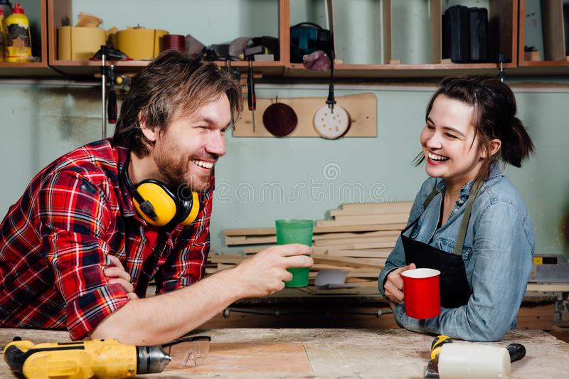 Carpenters having break from their work in wood workshop royalty free stock photography