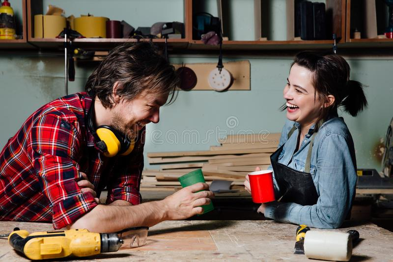 Carpenters having break from their work in wood workshop stock images