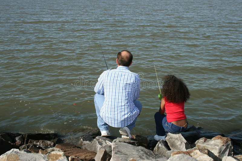 Man and girl fishing. A view of a man and young girl, sitting on a rocky riverbank, fishing royalty free stock photo
