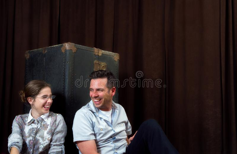 Man and Girl Lean Against an Old Steamer Trunk and Laugh royalty free stock image