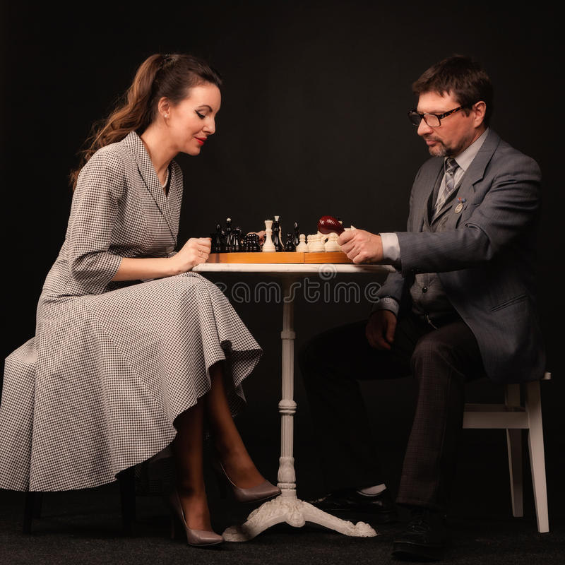 A man with a girl plays chess and smokes a pipe on a dark background stock photo