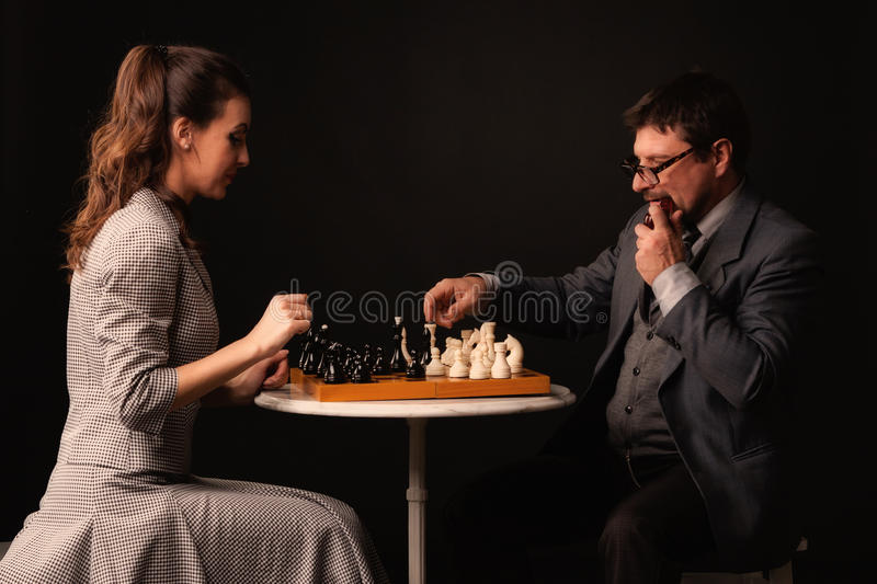 A man with a girl plays chess and smokes a pipe on a dark background royalty free stock images