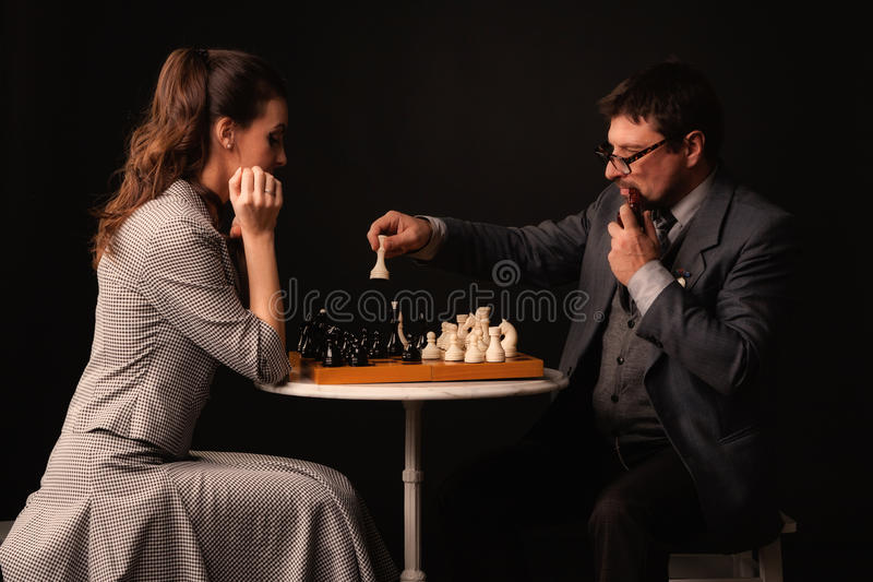 A man with a girl plays chess and smokes a pipe on a dark background stock images