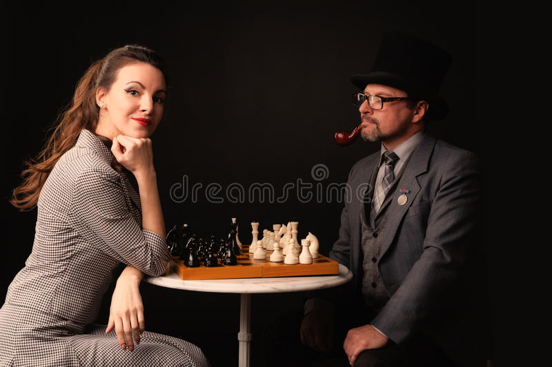 A man with a girl plays chess and smokes a pipe on a dark background stock image