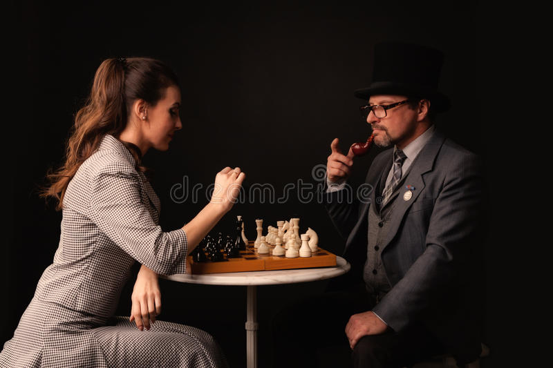 A man with a girl plays chess and smokes a pipe on a dark background royalty free stock photo
