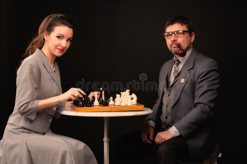 A man with a girl plays chess and smokes a pipe on a dark background royalty free stock photos