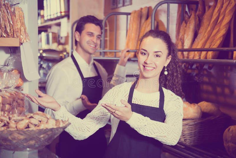 Man and girl selling pastry and loaves stock image