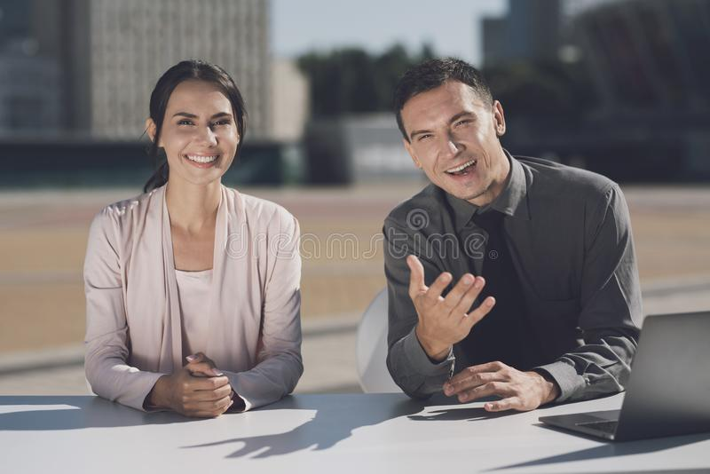 A man and a girl are sitting at a table in the city. He tells something and sits next to the laptop. TV reporters at work. A girl with folded arms smiling royalty free stock photos