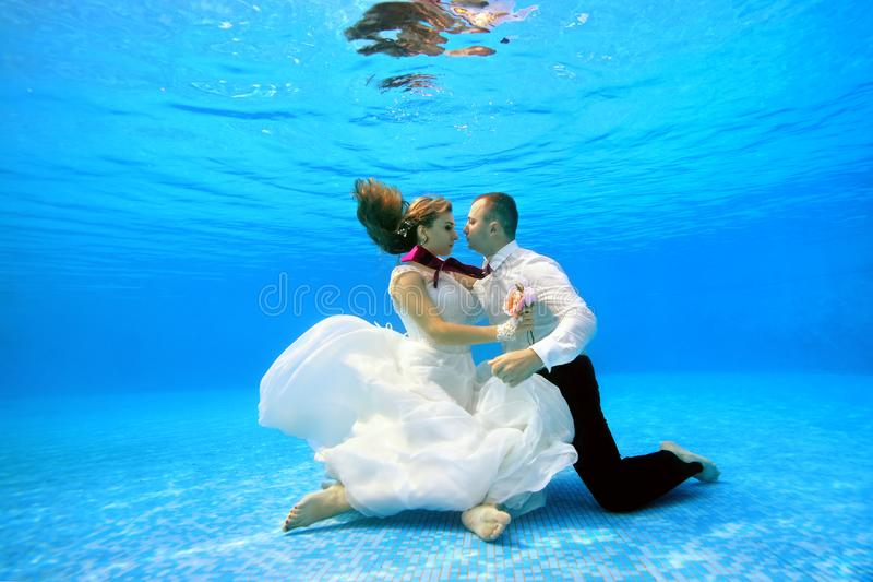 A man and a girl in wedding dresses hugging underwater and sit on bottom of pool. royalty free stock photo
