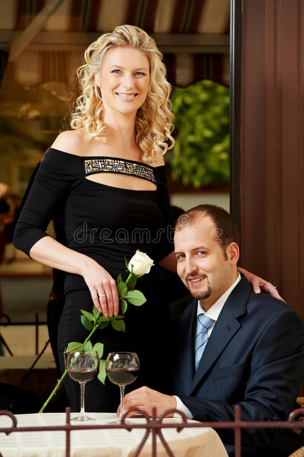 Man and girl with wine at cafe on royalty free stock photo