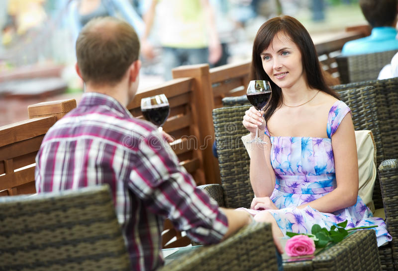 Man and girl with wine at cafe on a date stock image