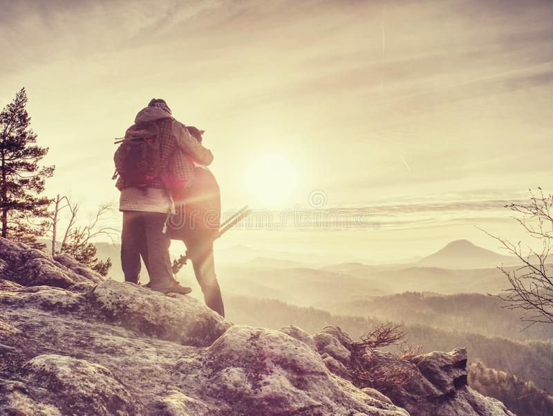 Man and girlfriend shooting sunset on the top mountain royalty free stock photo