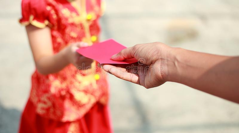 Close up hand give money in red envelop to girl on Chinese new year. Man give money in red envelop to girl on Chinese new year stock image