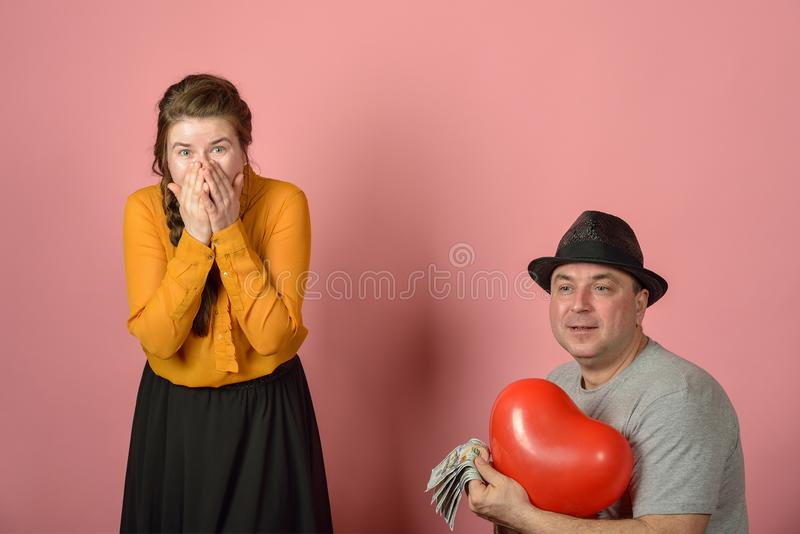 A man gives a balloon, in the form of the heart of his beloved, congratulations among lovers royalty free stock images