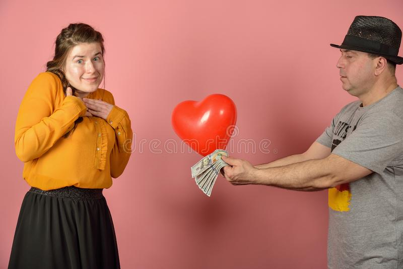 A man gives a balloon, in the form of the heart of his beloved, congratulations among lovers stock photos