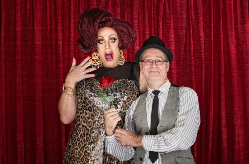 Man Gives Drag Queen a Rose. Retro men giving surprised drag queen a rose royalty free stock image