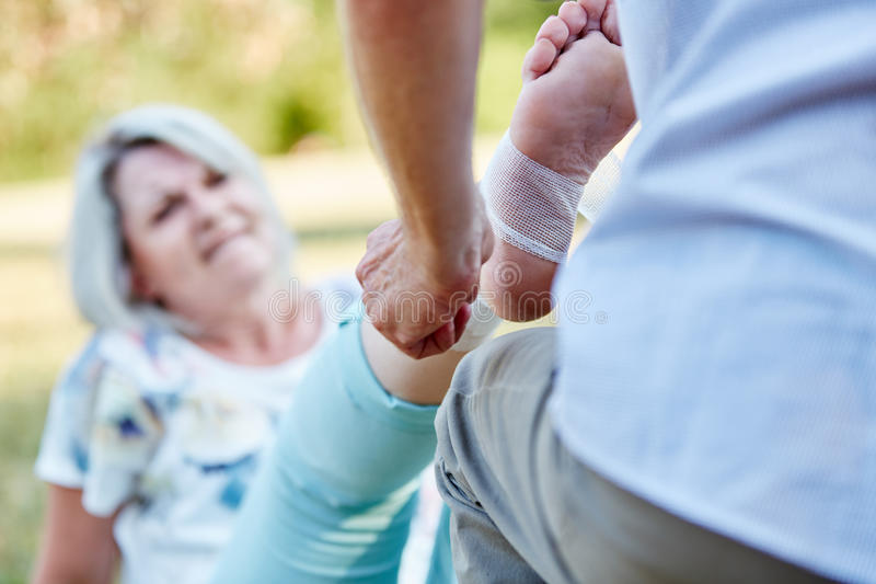 Man gives first aid help to a senior woman. Man gives first aid help to a senior women with a sprained ankle stock images