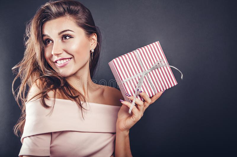 Happy beautiful woman with a gift box for Valentine's day on black background. royalty free stock photos