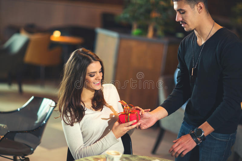 Man gives a gift to a young girl in the cafe. Young men gives a gift to a young girl in the cafe royalty free stock photos