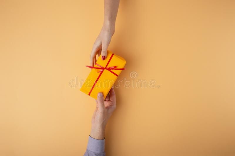 Man gives a girl a gift from hand to hand,box wrapped in decorative paper with a bow orange background, the concept of holidays, stock photography